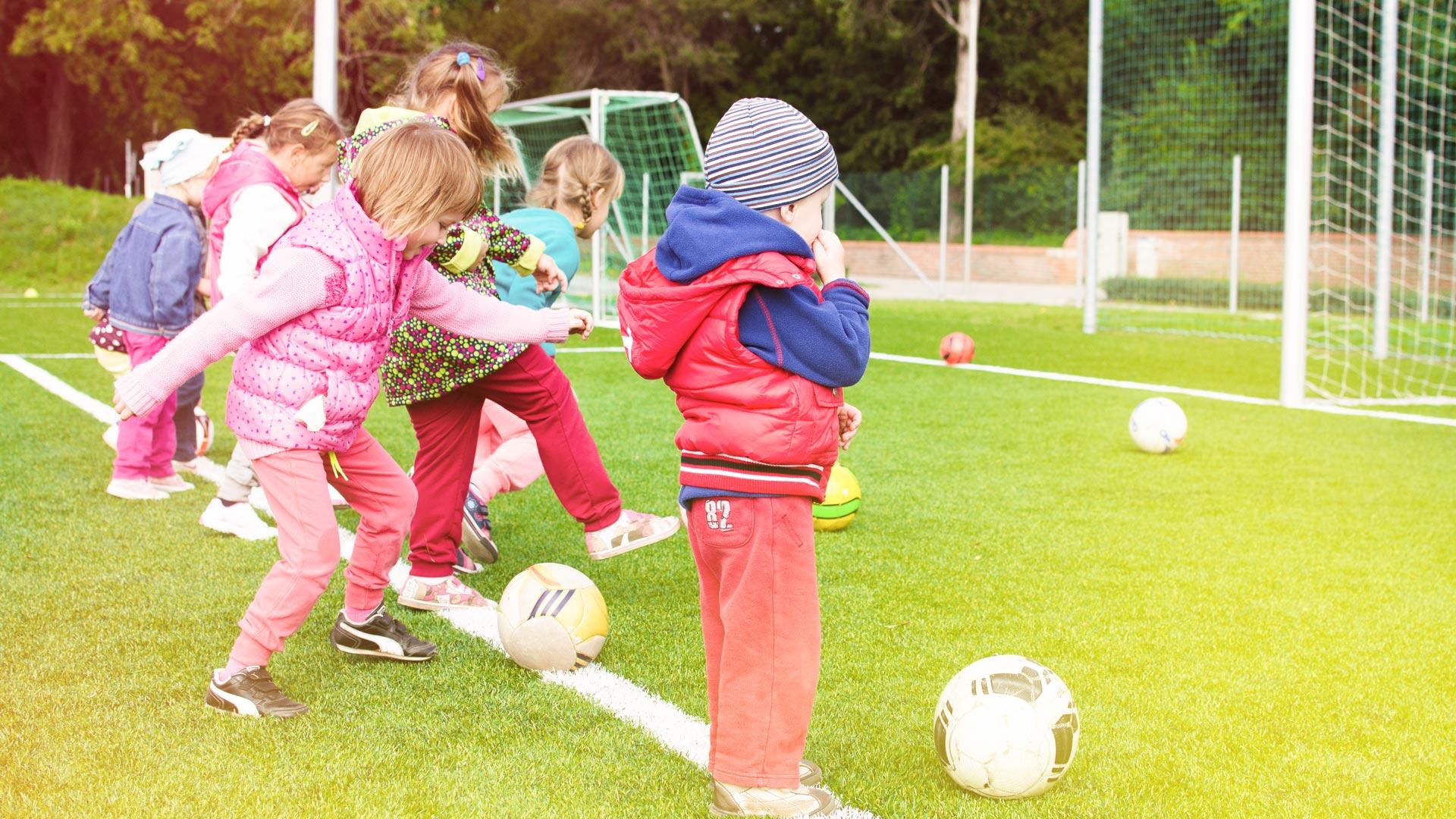 Firmeneigene Ferienprogramme Kinder spielen Fussball in den Ferien