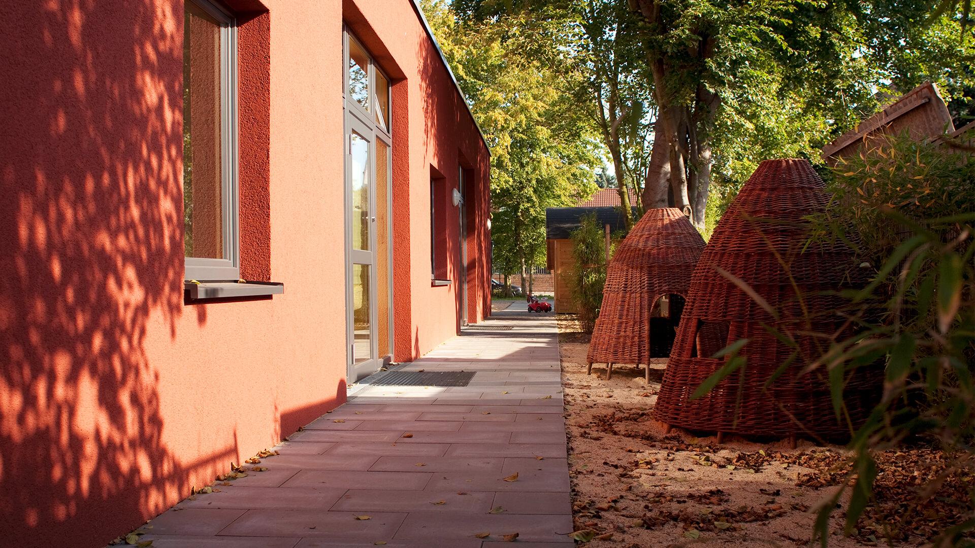 Sonnengeschützter Außenbereich der Kita mit Indianer-Zelten aus Rattan-Korbgeflecht