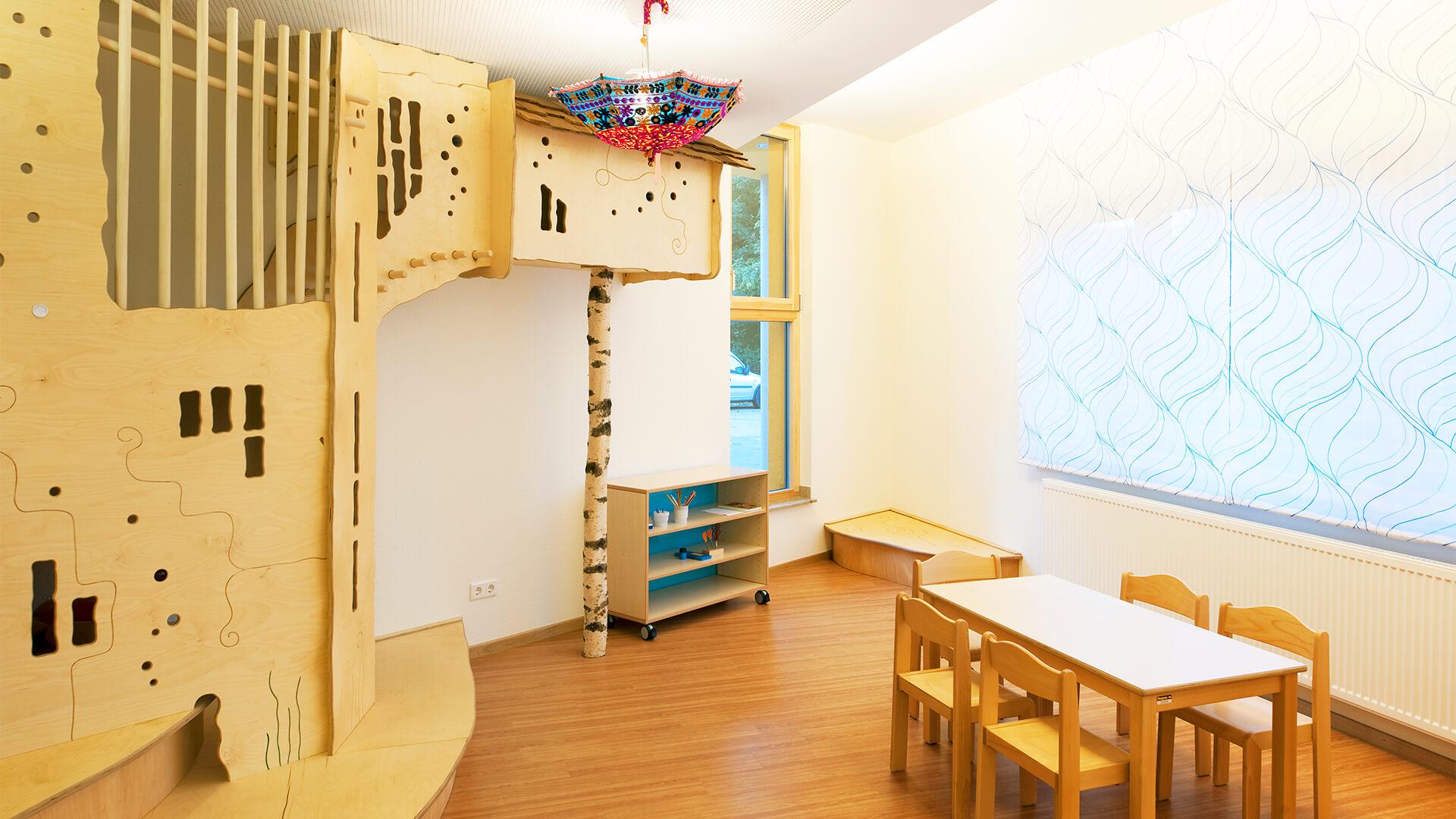 Kreativer Bereich mit Holzelemente, Birkenstämmen und bunten Regenschirmen an der Decke