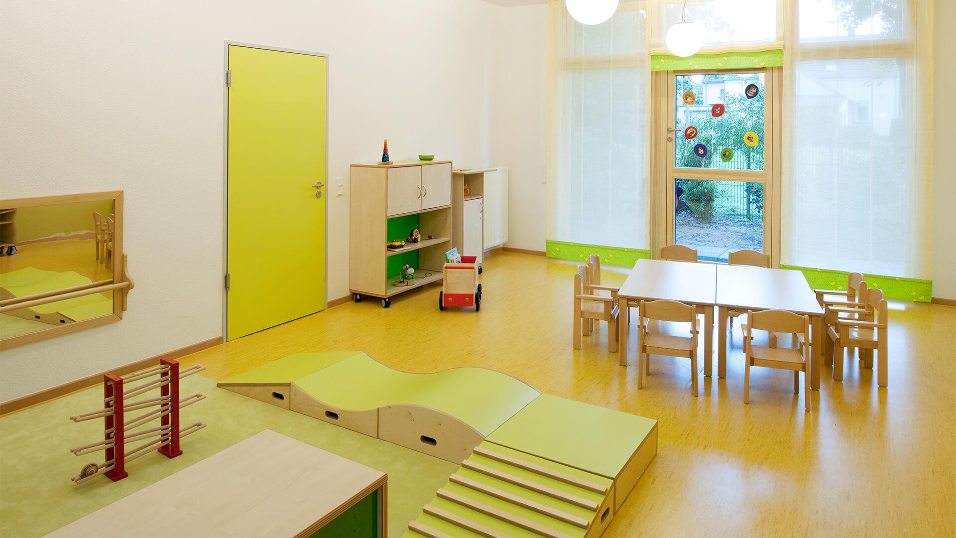 Gruppenraum der Kindertagesstätte in Neuss mit Tischen und Spielecke auf grünem Teppich