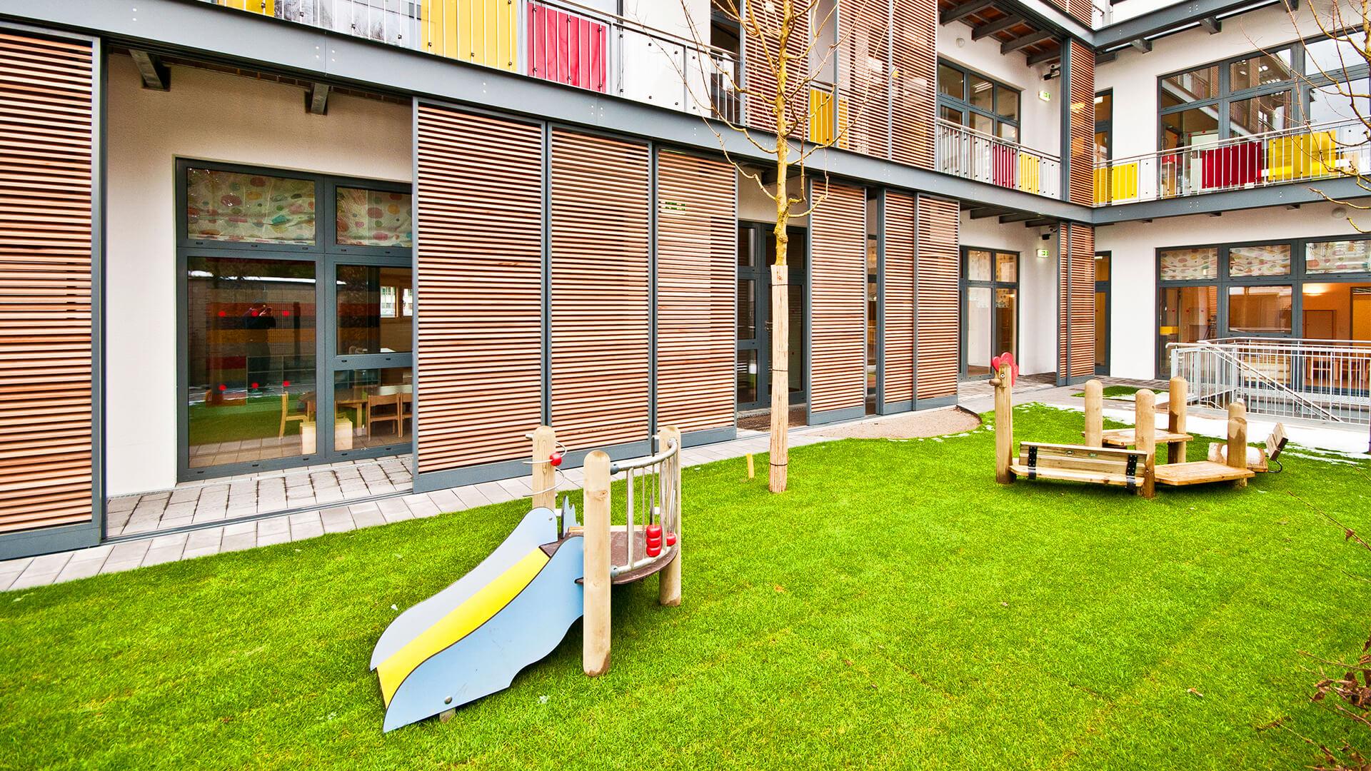 Supergrüne Außenanlage unserer Kita in Düsseldorf Heerdt – mit Wiese, Rutschen und modernen Schattenspendern