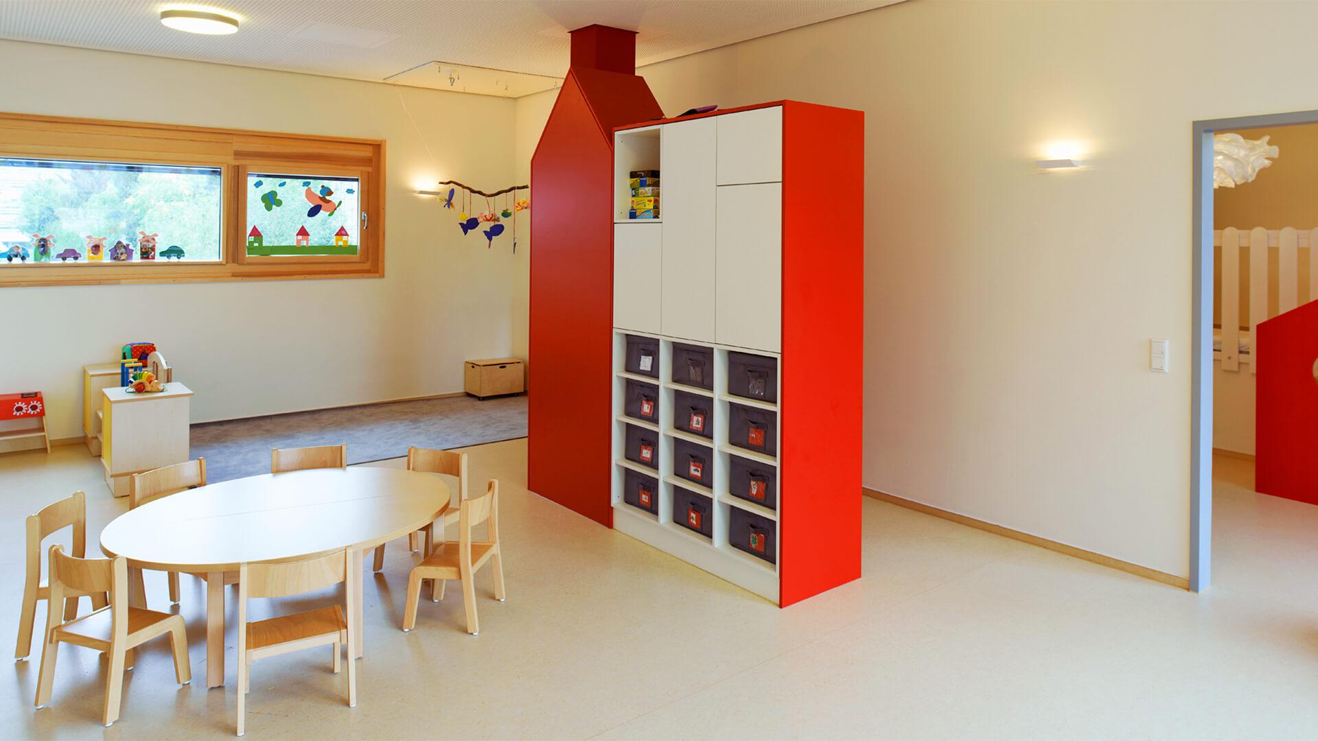 Spielecke, mit von Kindern gebastelter Fenster-Gestaltung und ein großer Spielzeug-Schrank