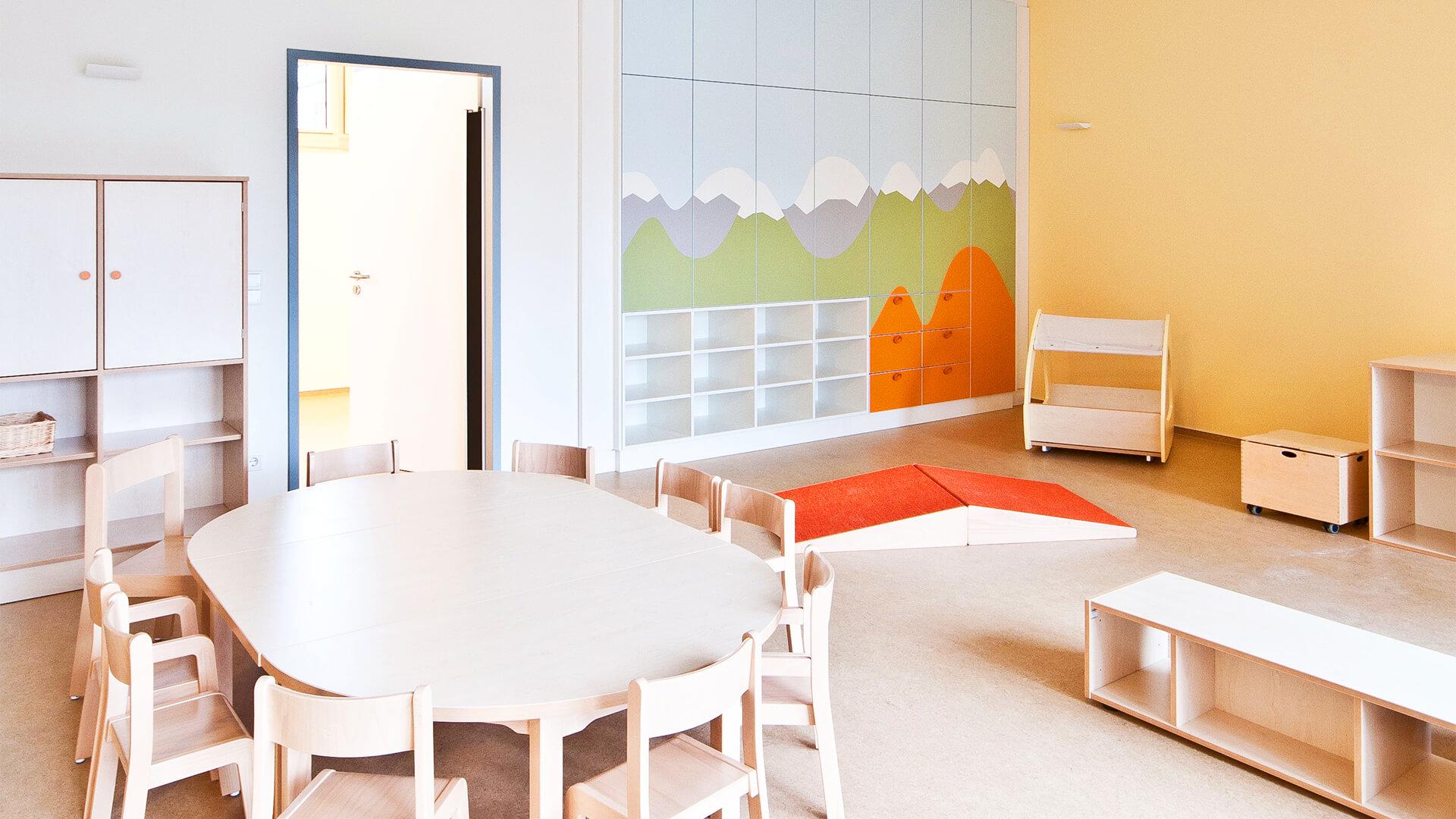 Gruppenraum mit runden Tischen und Stühlen für viele Kinder. Außerdem bemalte Schränke mit Bergmotiven