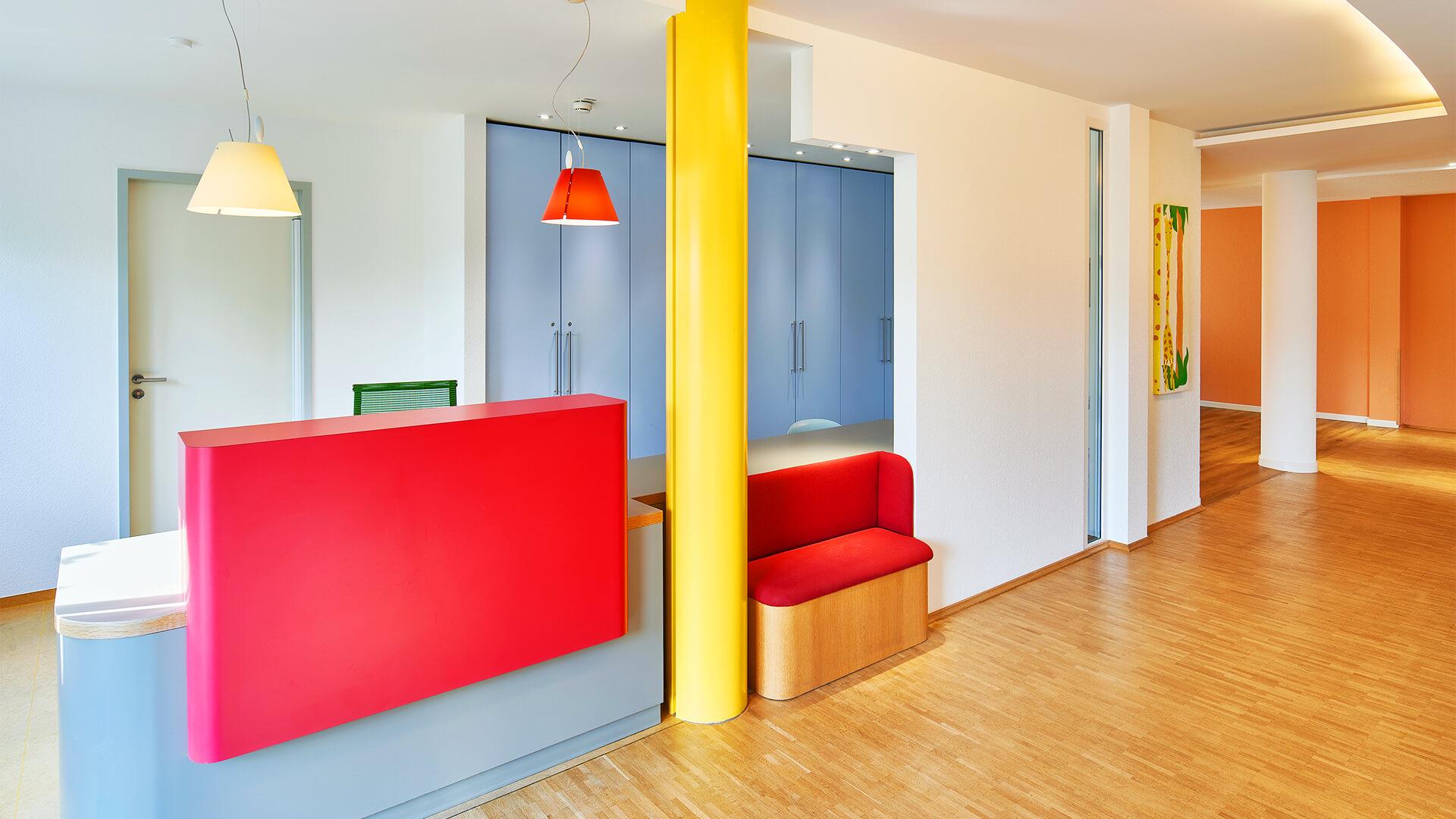 Flur / Empfang in rot, gelb und blautönen mit gemaltem Kinderbild an der Wand
