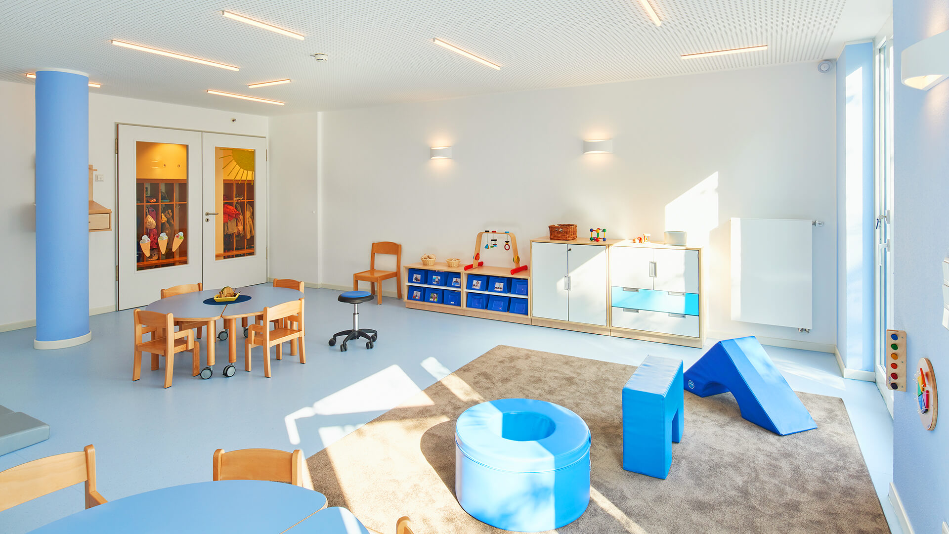 Freundlicher, blauer Innenraum mit Teppich und Spielmöglichkeiten