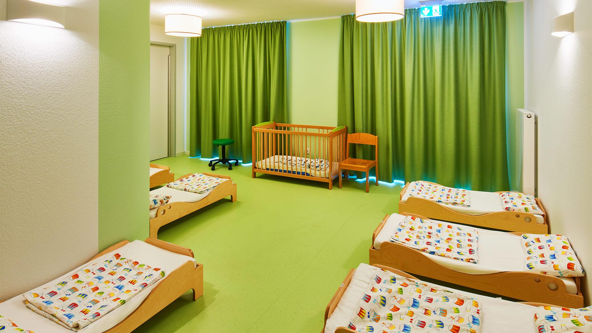 Grüner Ruheraum der Kita in Neuss, mit Betten für kleine und große Kinder