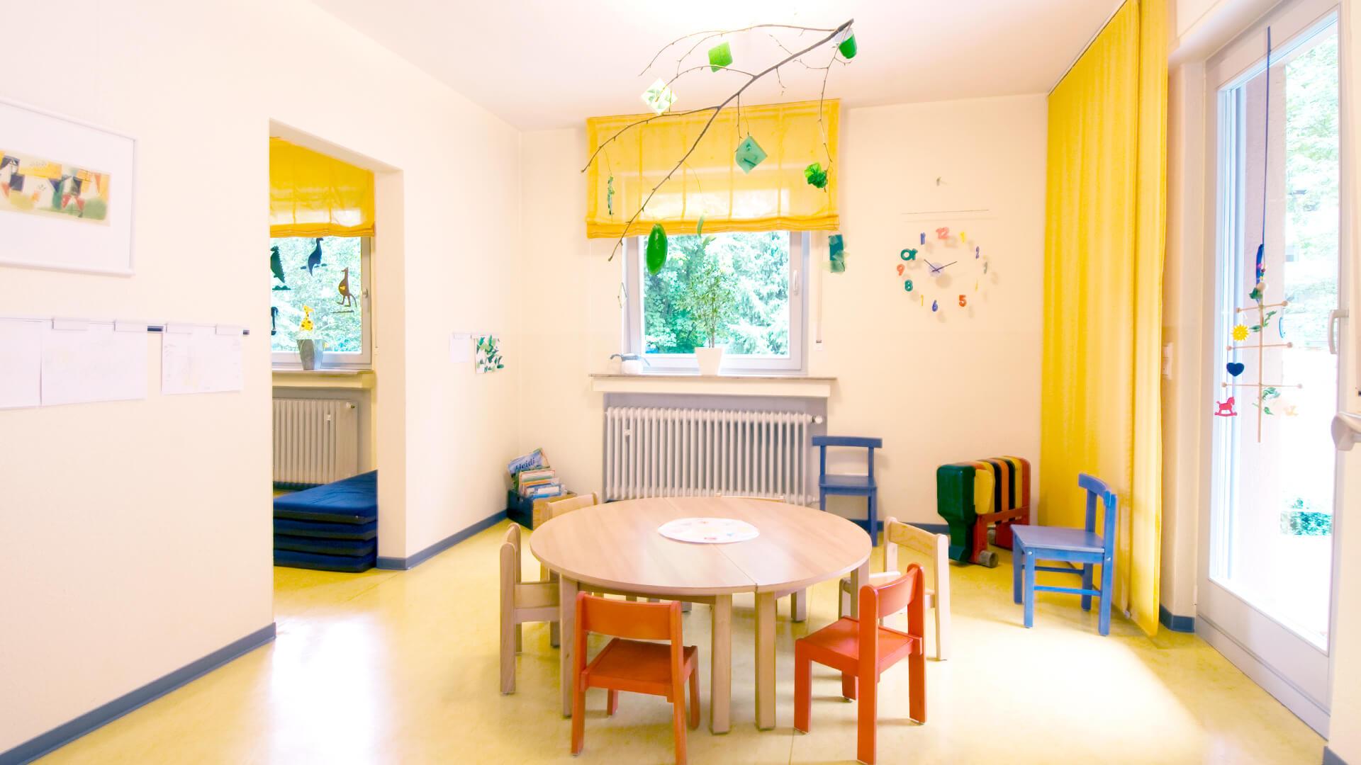 Sonnen-gelber Kita-Innenraum mit Lern-Uhr und Natur-Mobile an der Decke