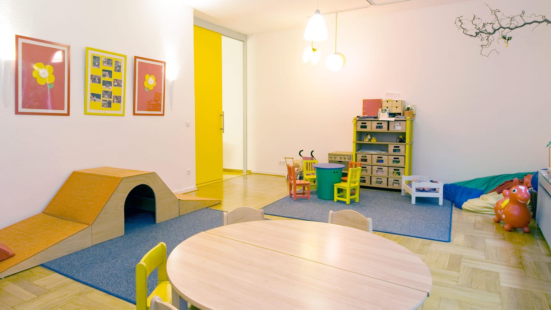 Gruppenraum der Kindertagesstätte mit runden Tischen, Spiele-Regal und Kuschelecke