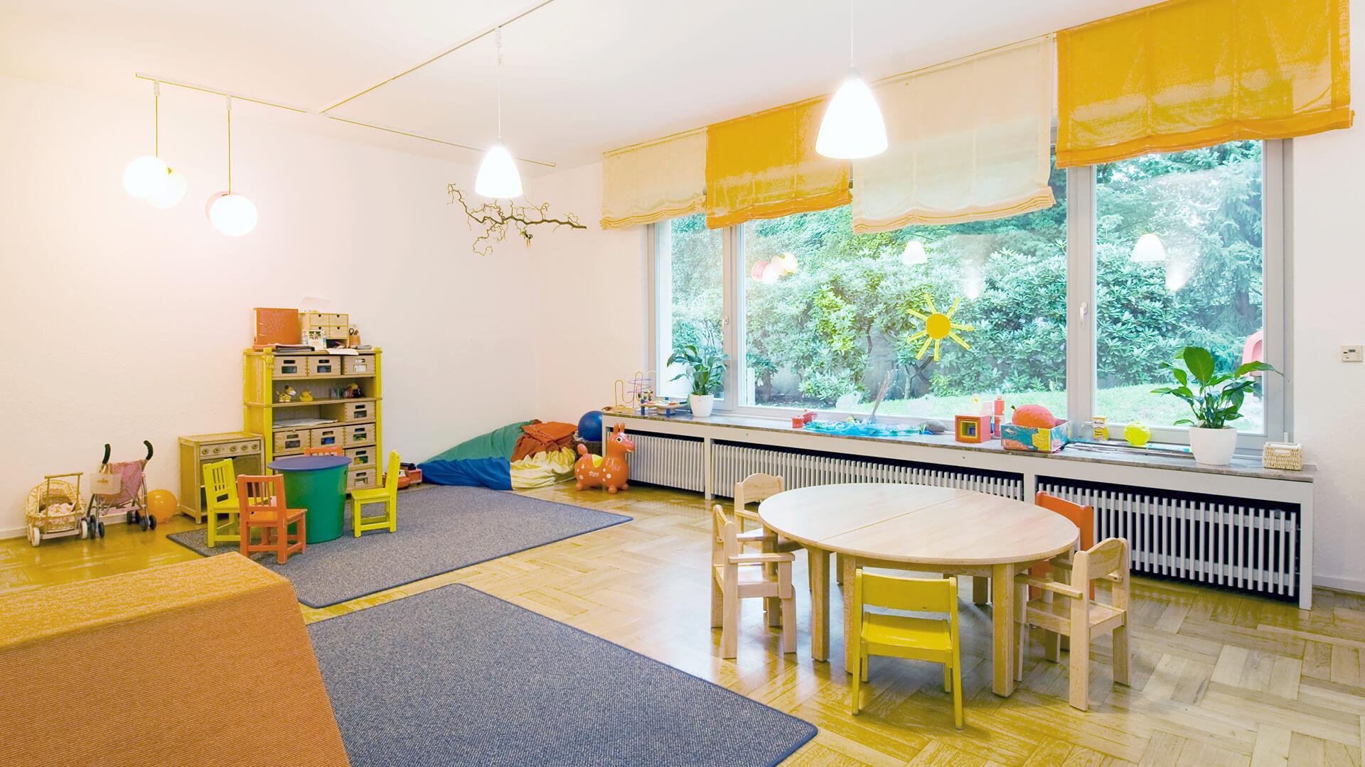 Kita-Gruppenraum mit großen Fenstern, Kinderwägen und Basteltisch für mehrere Kinder