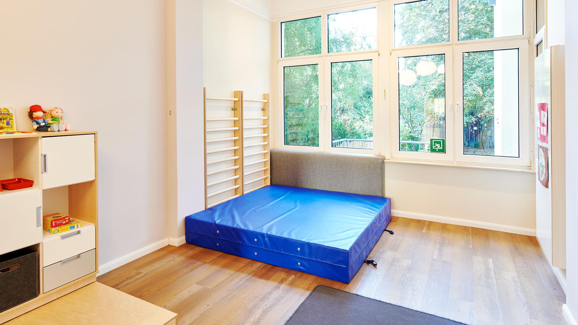 Klettergerüst in der Turnecke zum austoben mit dicker, blauer Turnmatte auf dem Boden