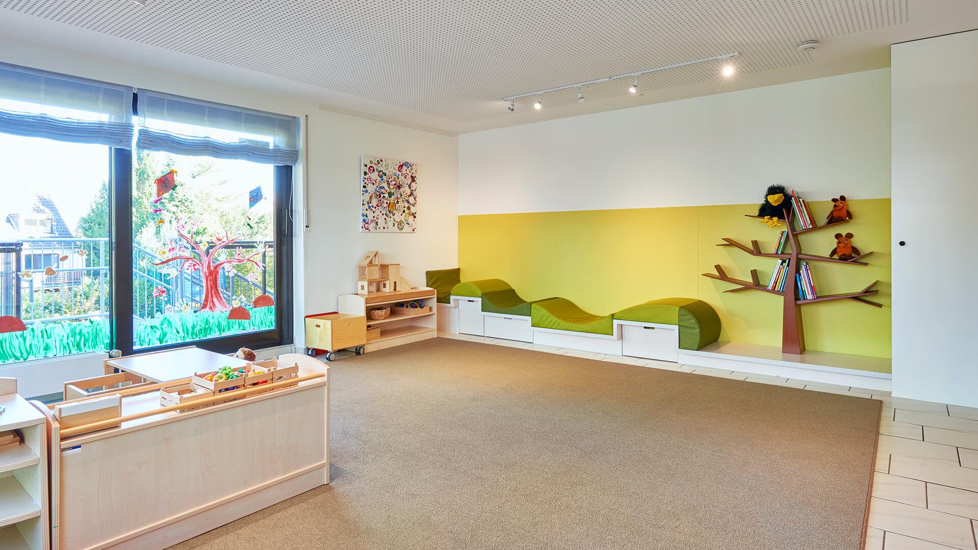 Gruppenraum der Kita mit großen, bemalten Fenstern, weichem Teppich und Bildern an den Wänden