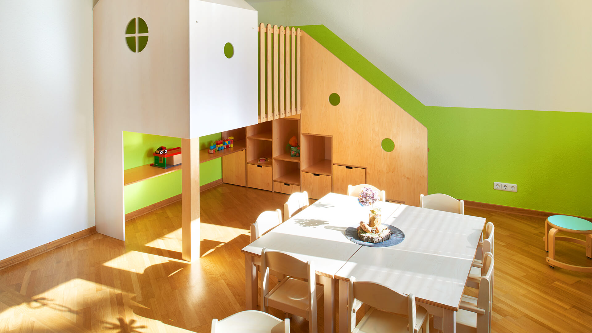 Freundlich-grüner Essbereich mit Sonnenschein und Stühlen für viele Kinder