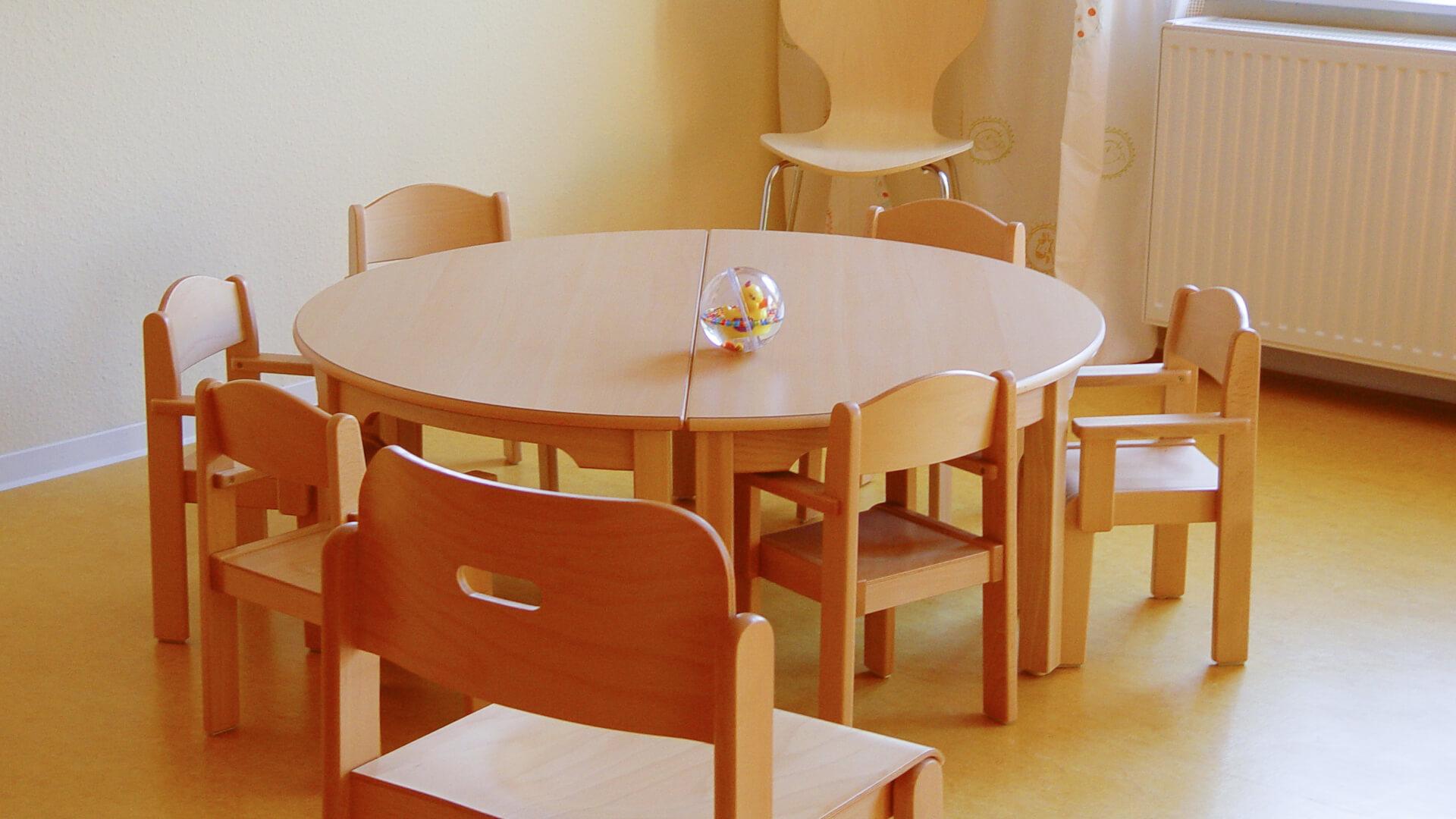 Runder Holztisch mit Stühlen für viele Kinder