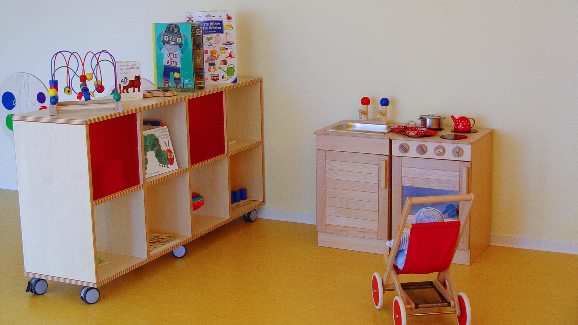 Spielküche, Kinderwagen mit Puppe und Bilderbücher