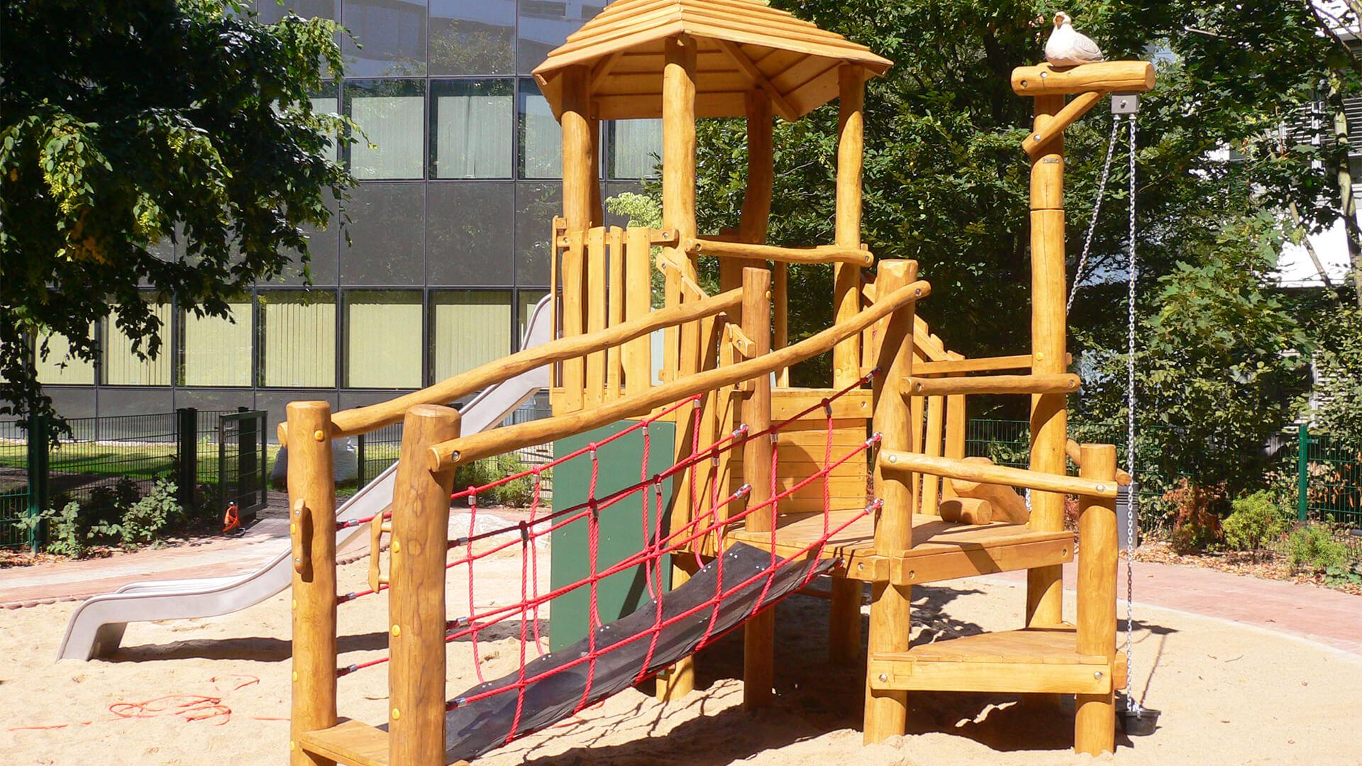 Spielplatz mit Sandkasten, Klettermöglichkeiten und Rutsche