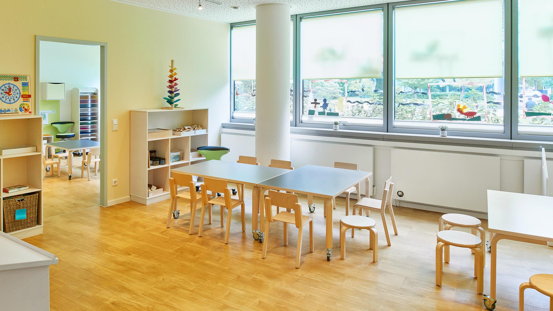 Große bemalte Fenster, Lern-Spielzeug und Tische mit Platz für viele Kinder