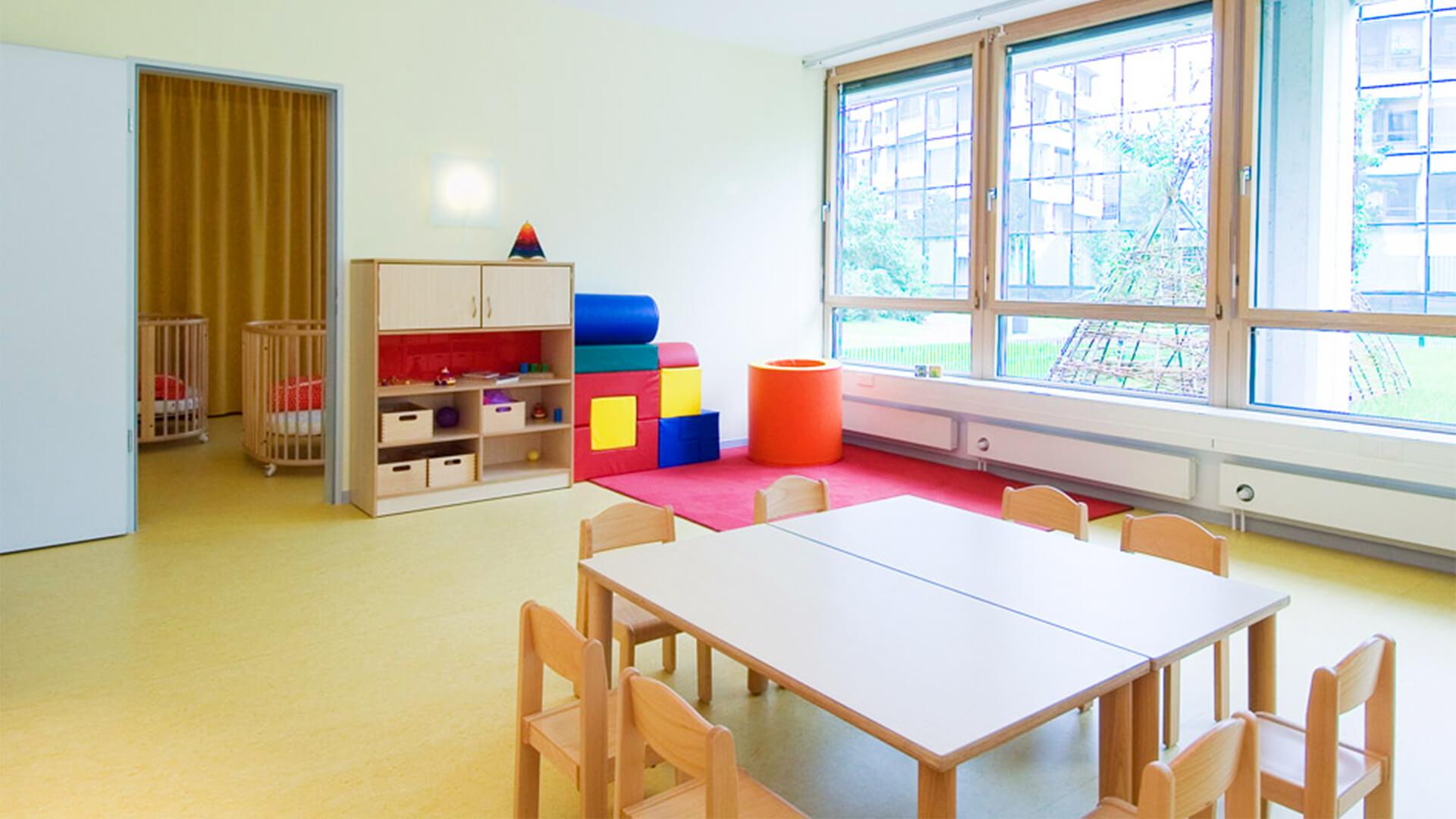Heller Gruppenraum der Kita in Düsseldorf, mit großen Fenstern