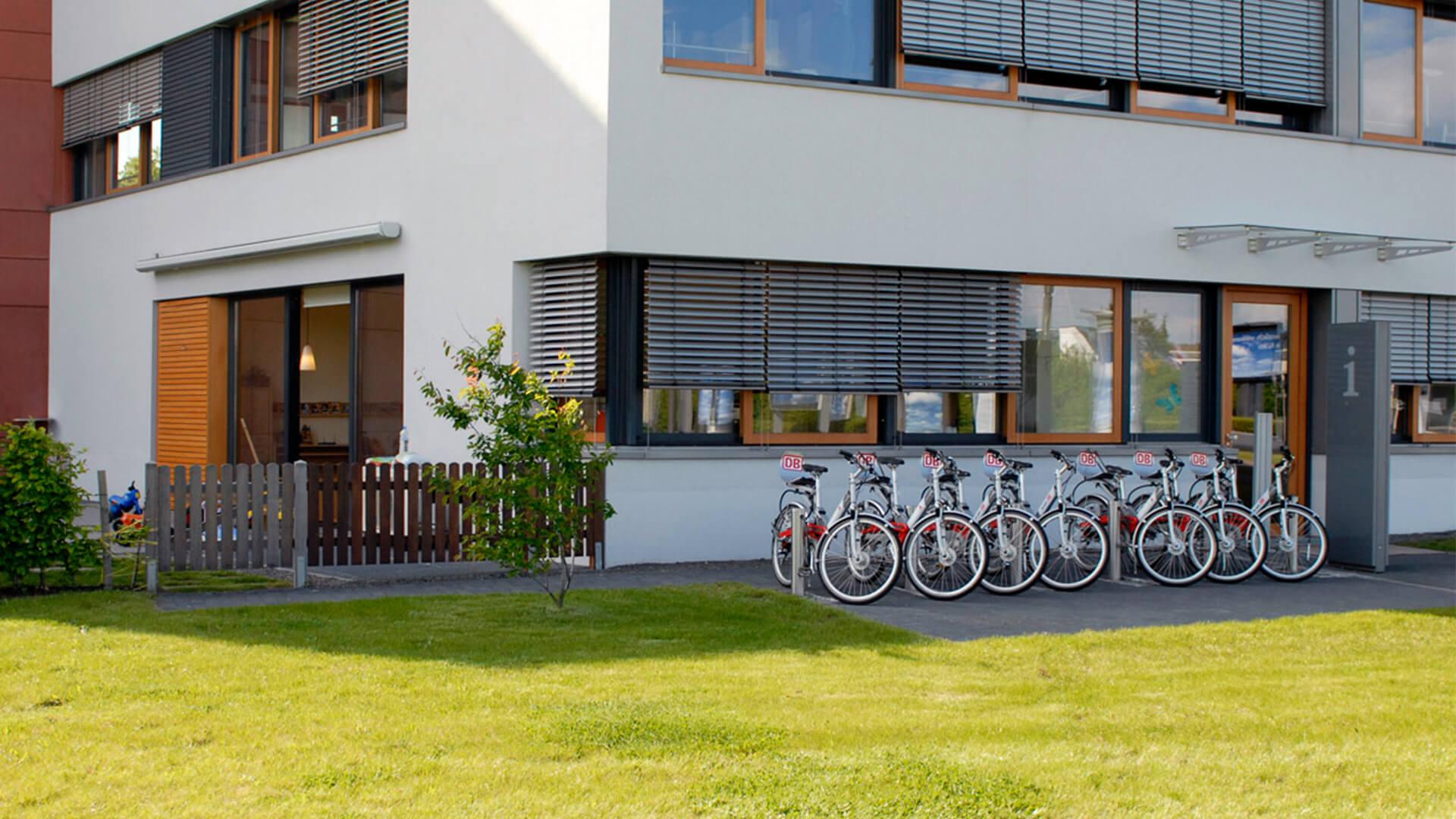 Fahrräder vor dem Kindergarten mit moderner Außenfront, Wiese und Sonnenschein