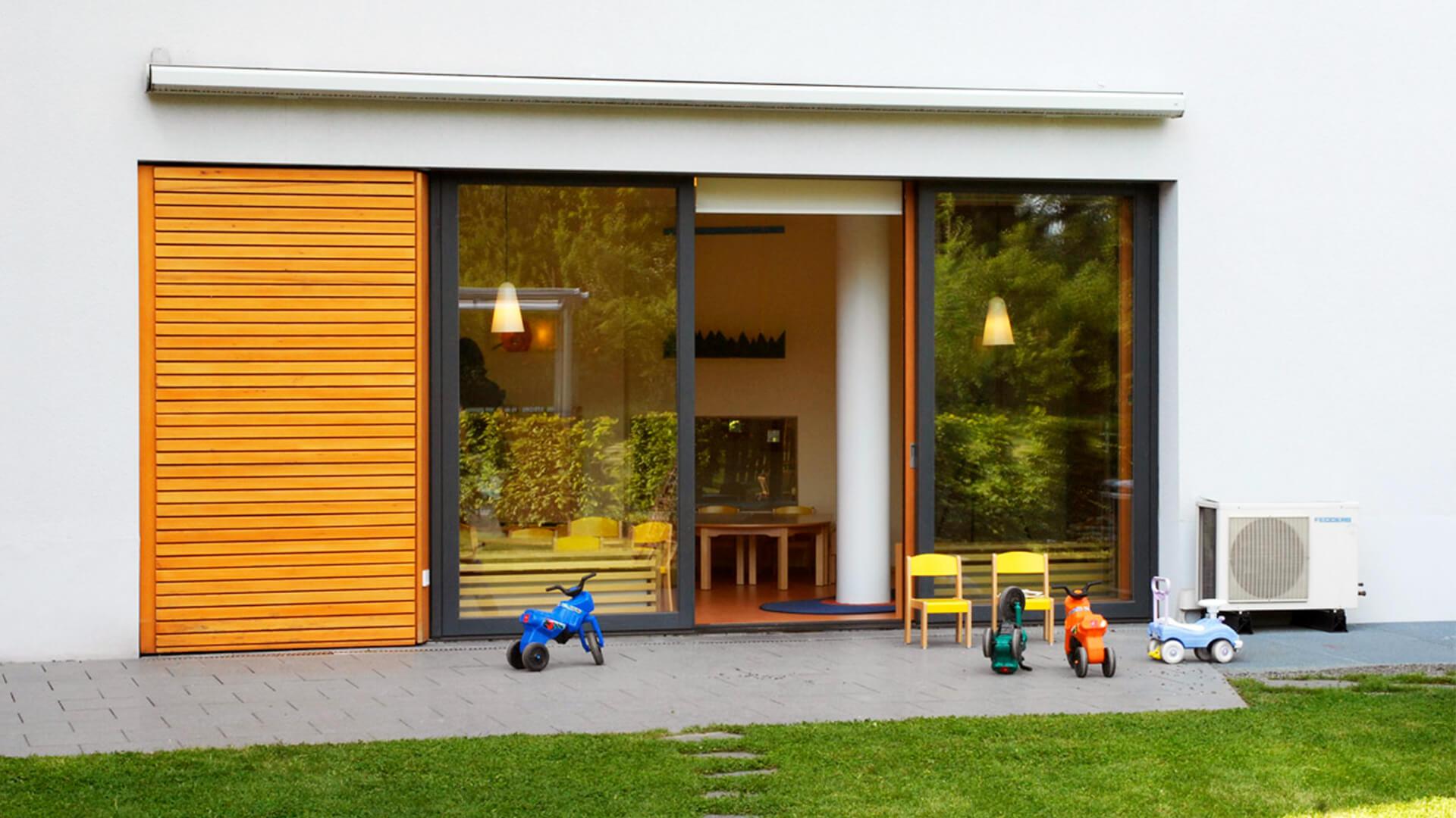 Terrasse des Betriebskindergarten in Köln - mit Bobbycars und Wiese