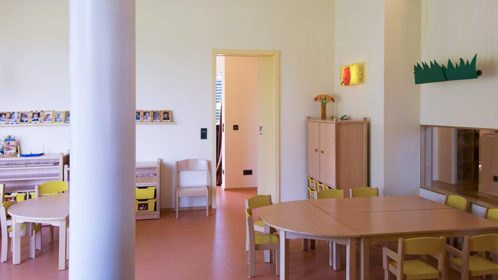 Gruppenraum mit runden Tischen und Stühlen für viele Kinder
