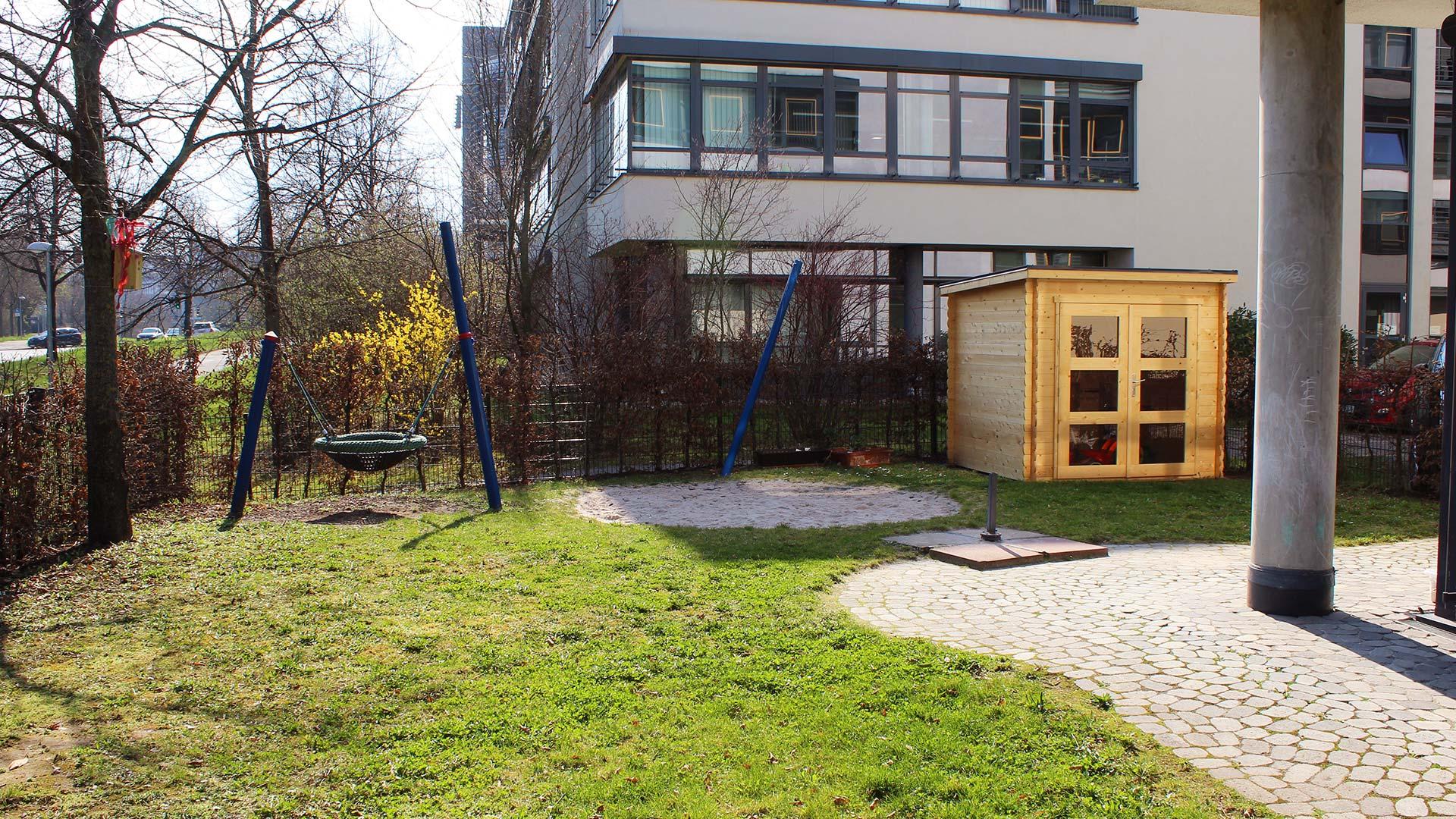 Außenansicht des Spielbereichs mit Wiese im Vordergrund und Babyschaukel