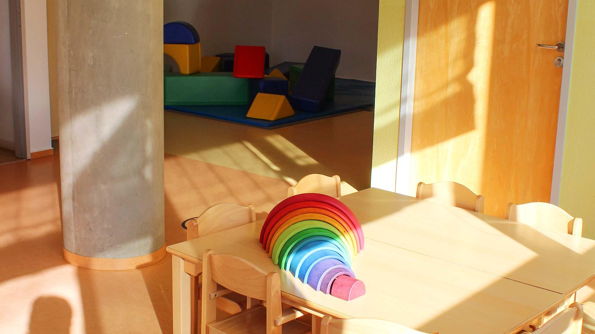 Raum mit einem Tisch auf dem Spielzeug liegt im Hintergrund Blick durch eine geöffnete Tür in den Turnbereich des Kindergartens