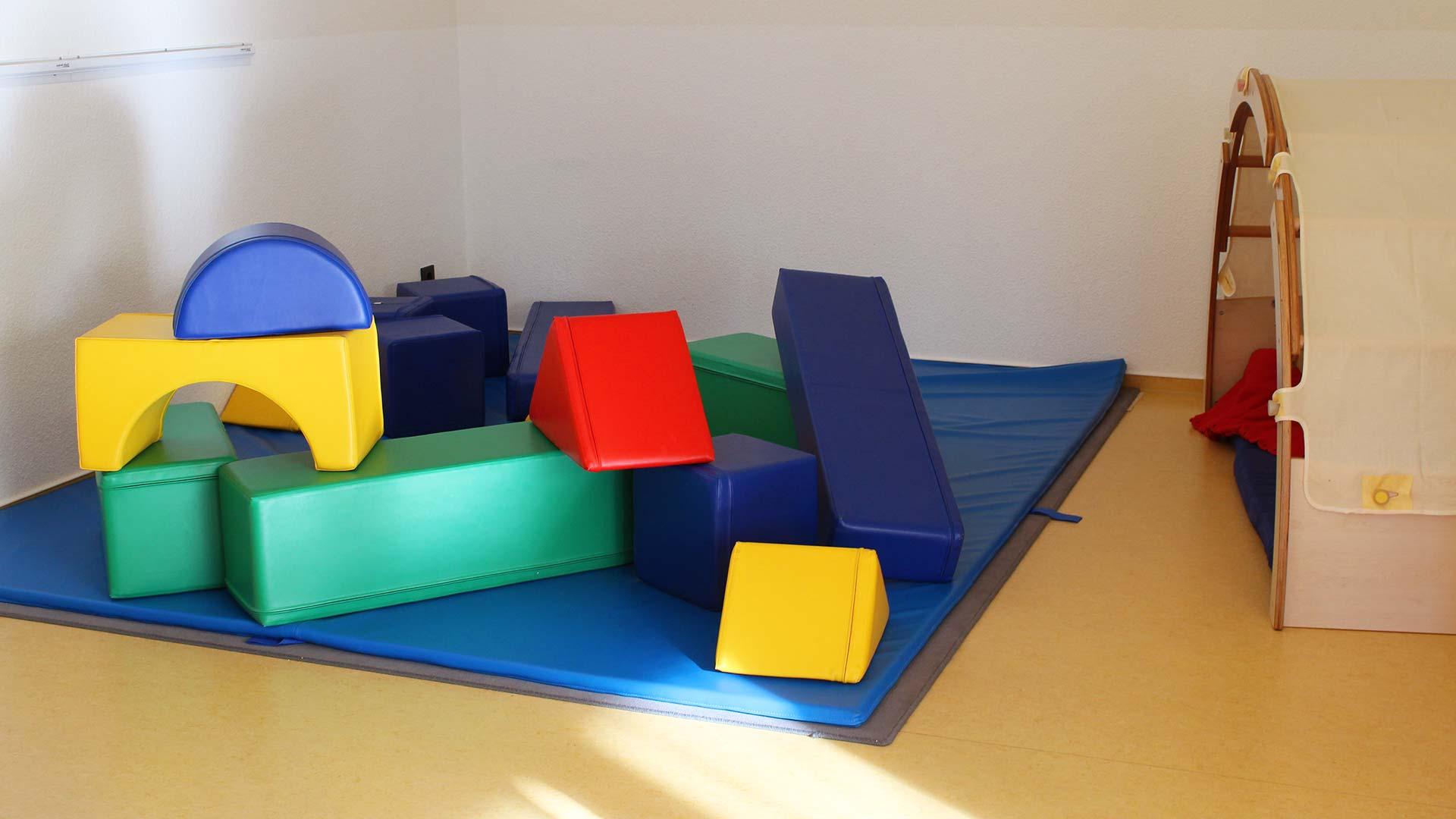 Turnbereich bzw. Tobeecke mit Matte auf dem Boden und übergroßen Bauklötzen aus Schaumstoff