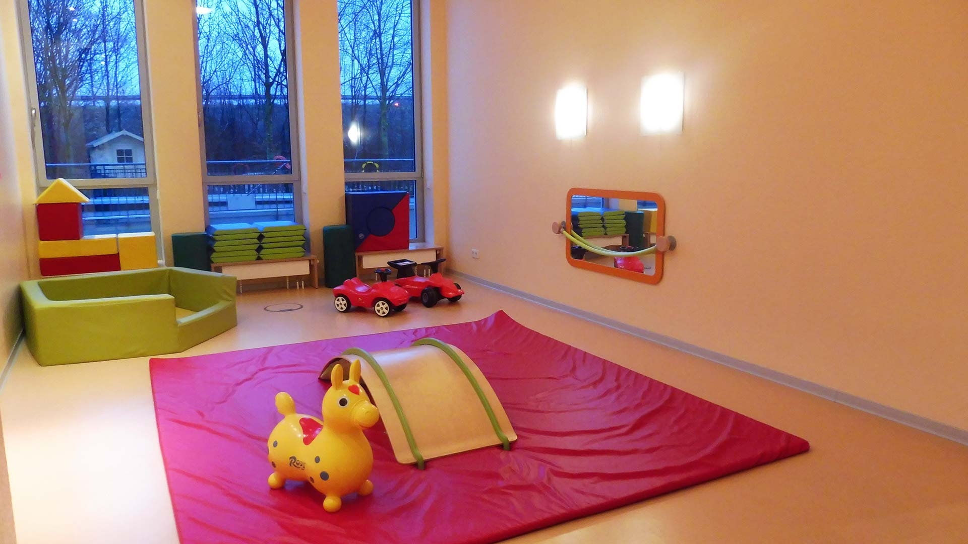 Spielzimmer mit Turnmatte und Spielzeug für die Kleinen