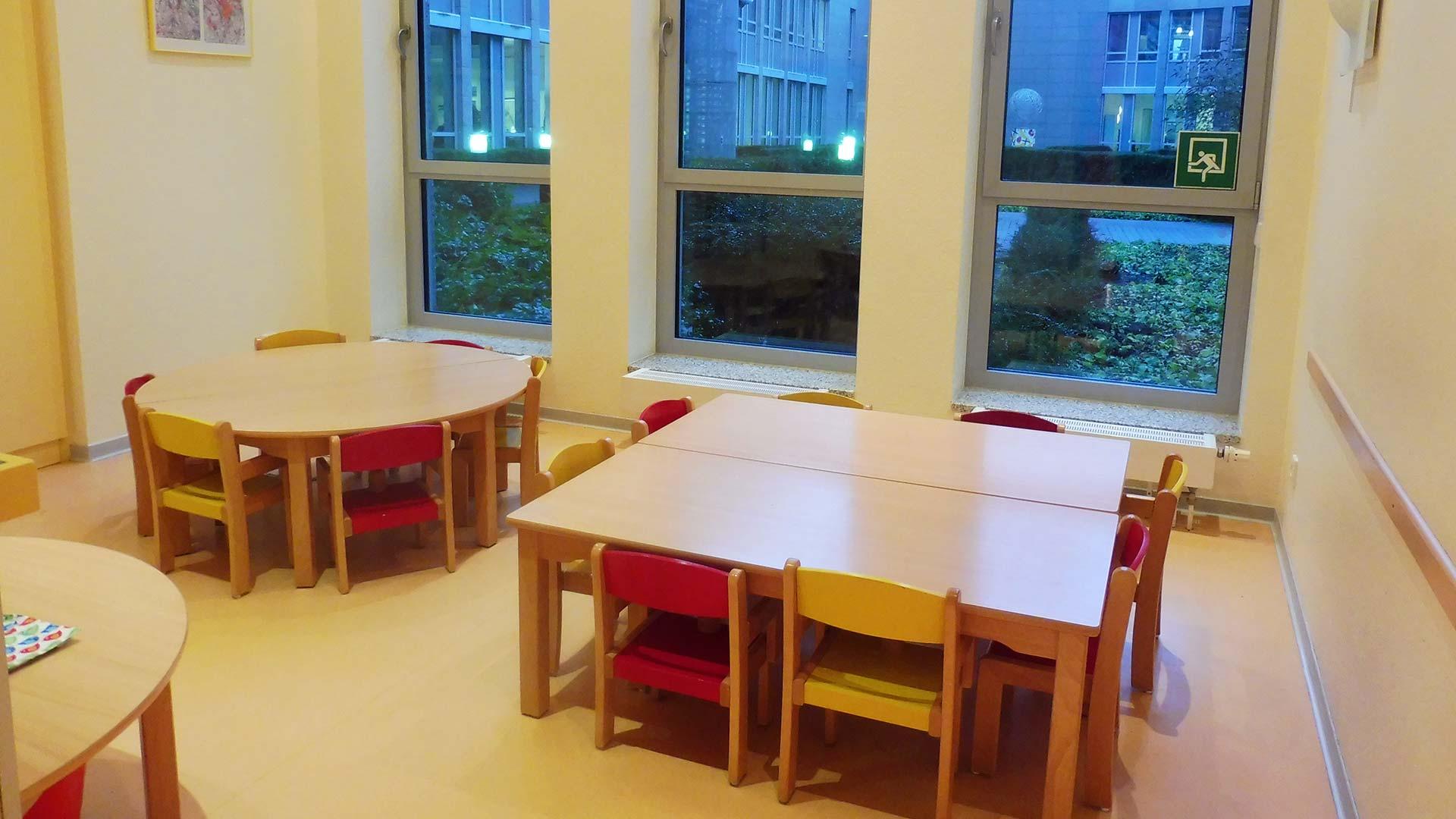 Esszimmer mit kleinen Tischen und Stühlen an dem die Kinder Platz zum essen finden