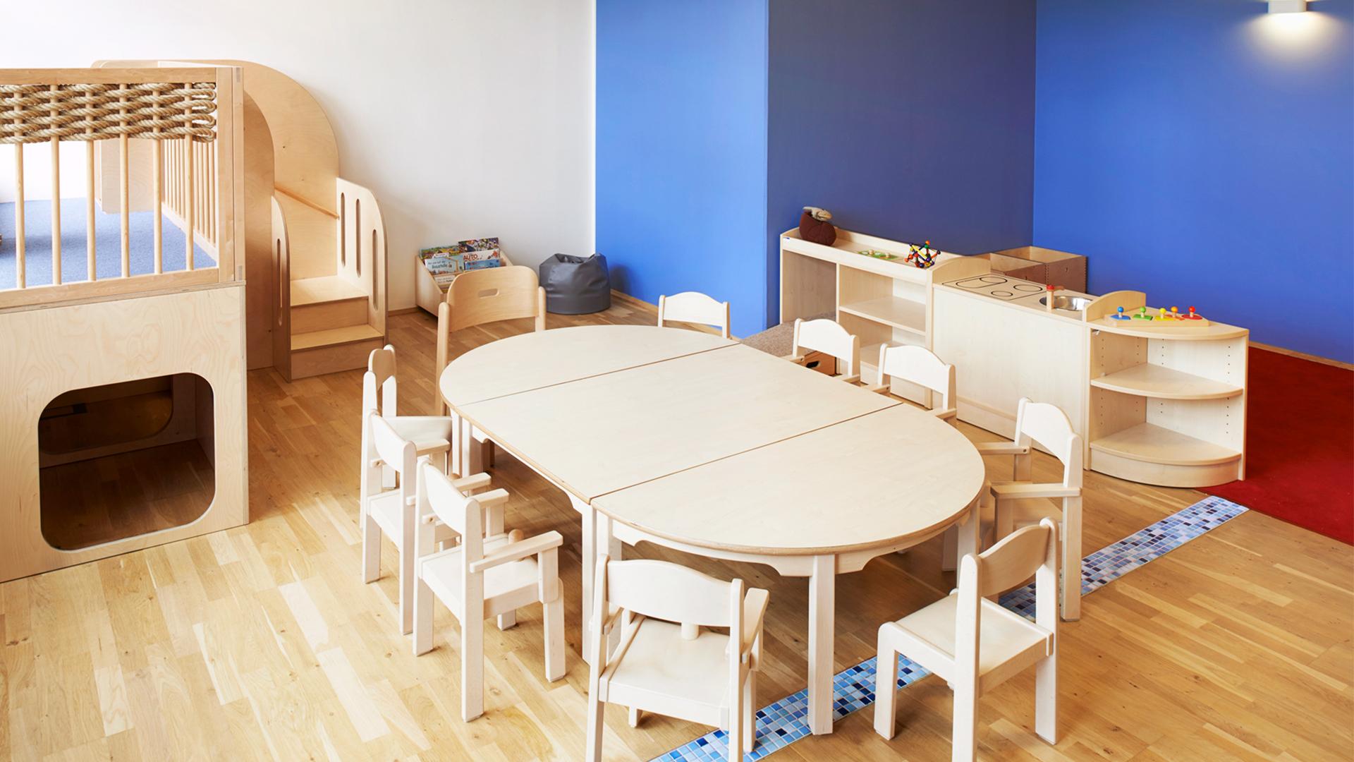 Spielküche und ein großer, runder Tisch mit Platz für viele Kinder