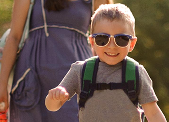 Fröhliches Kind auf Ausflug mit Sonnenbrille und Mutter bei Sonnenschein