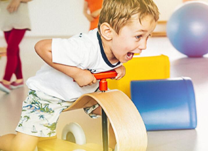 Kind auf Holz-Bobbycar beim aktiven Spiel in der Kindertagesstätte