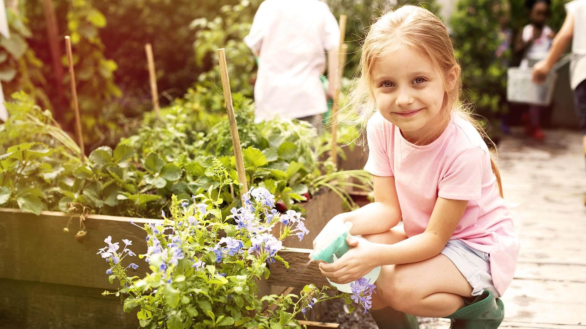 Erfahrungen sammeln beim gemeinsamen pflegen des Blumen- und Erdbeerbeets an der frischen Luft