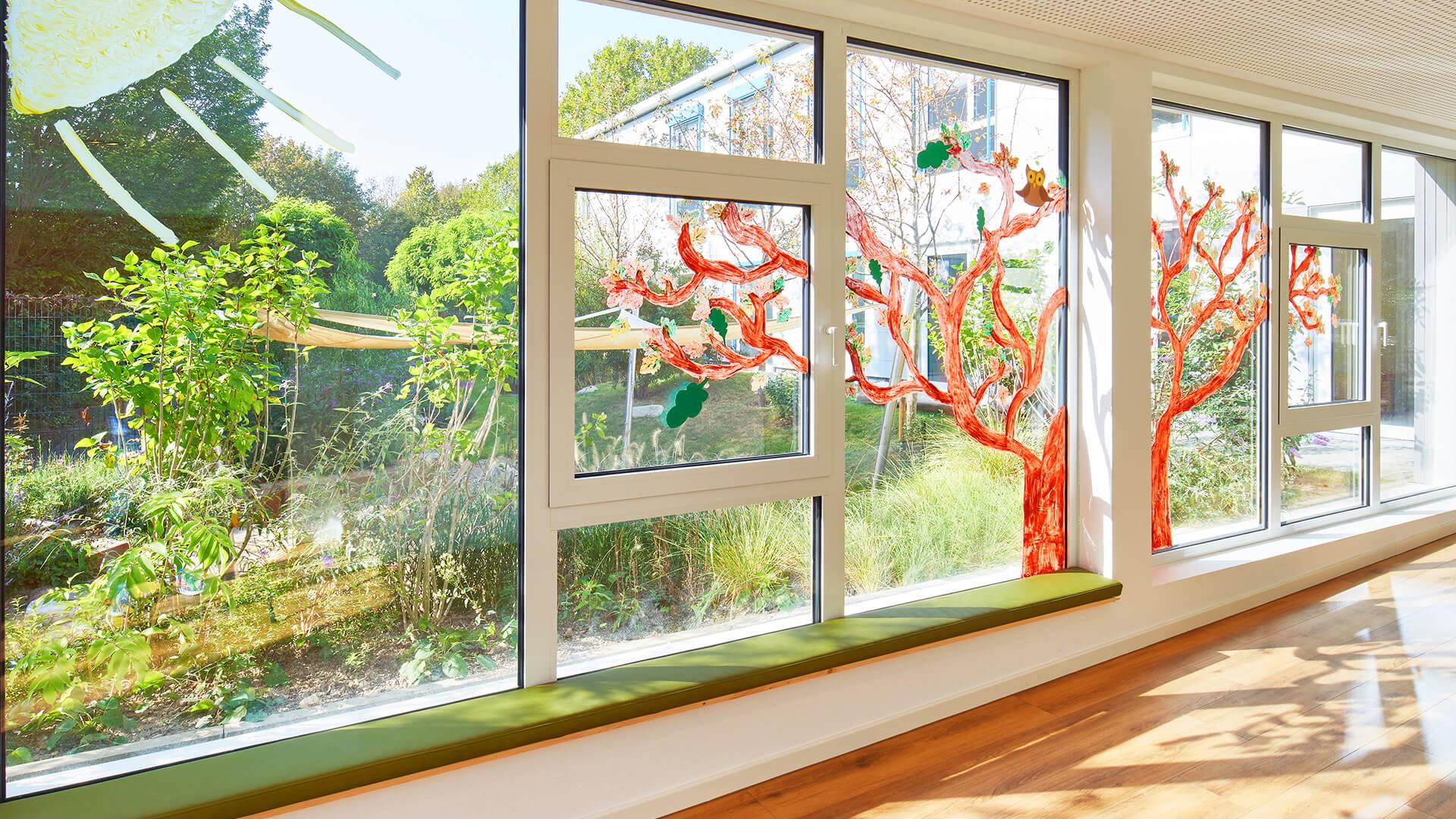 Große, von den Kindern bemalte Fenster mit Sonne, Baum und einer Eule. Blick auf den großzügigen Garten.