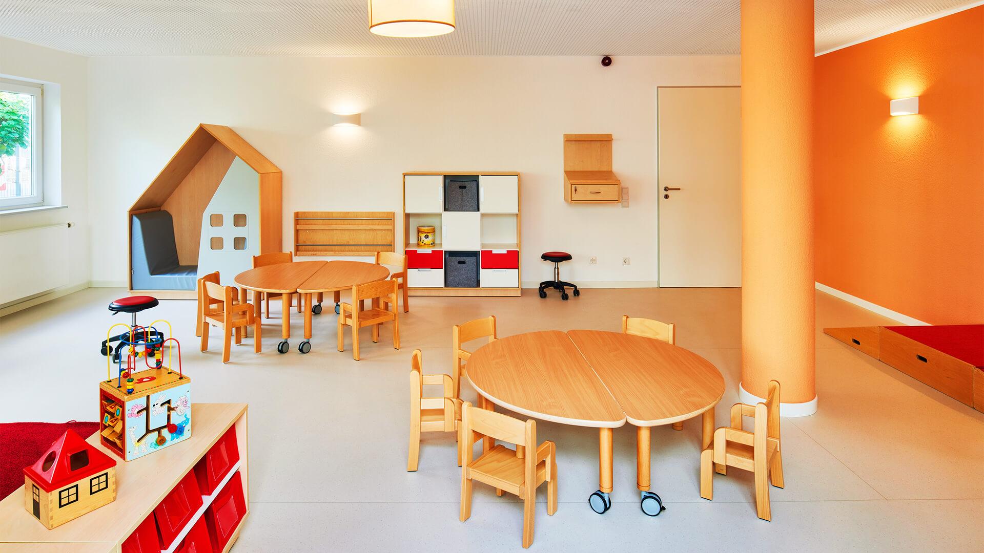 Gruppenraum mit Spiel- und Lese-Ecken und Runden Tischen mit Platz für viele Kinder
