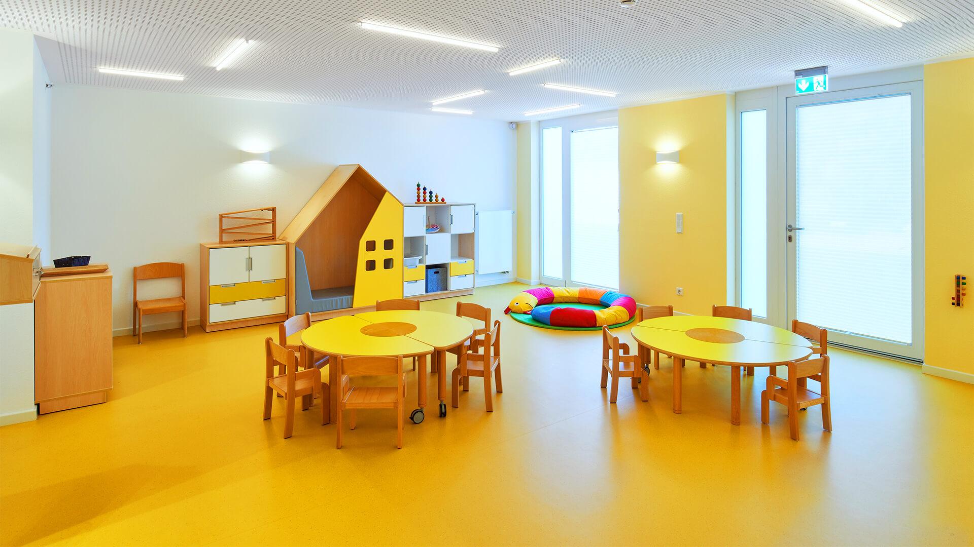 Sonnengelber Raum in einem Betriebskindergarten mit Sitzkreis und Kinderstühlen