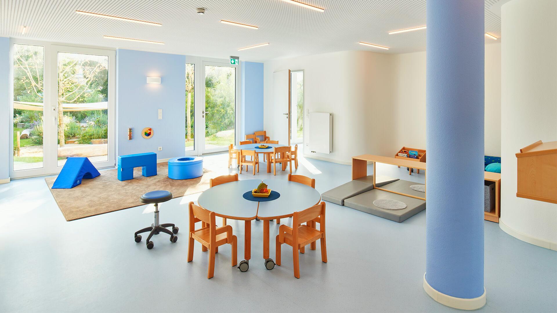 Freundlich-moderner Betriebskindergarten von innen - in blautönen, mit weichen Sitzmöglichkeiten.