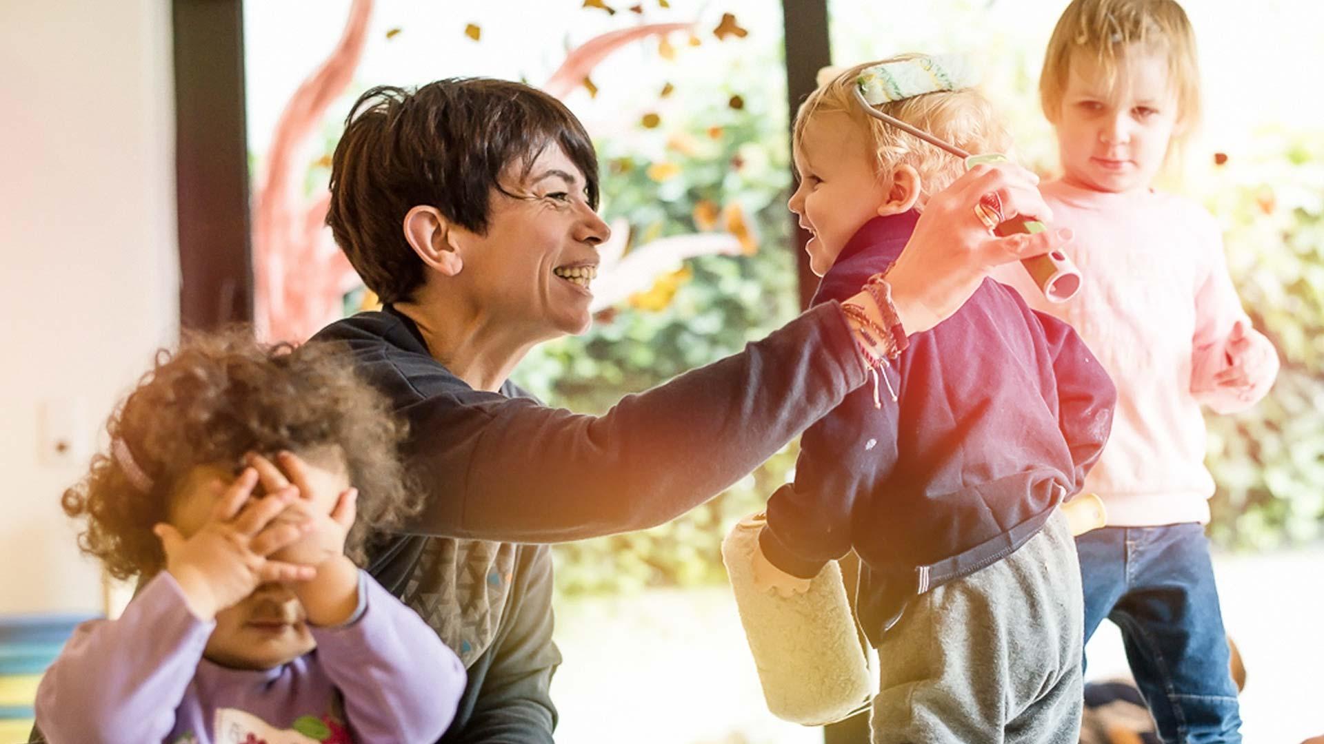 Pädagogischer Ansatz Kita Betreuerin spielt mit drei Kindern