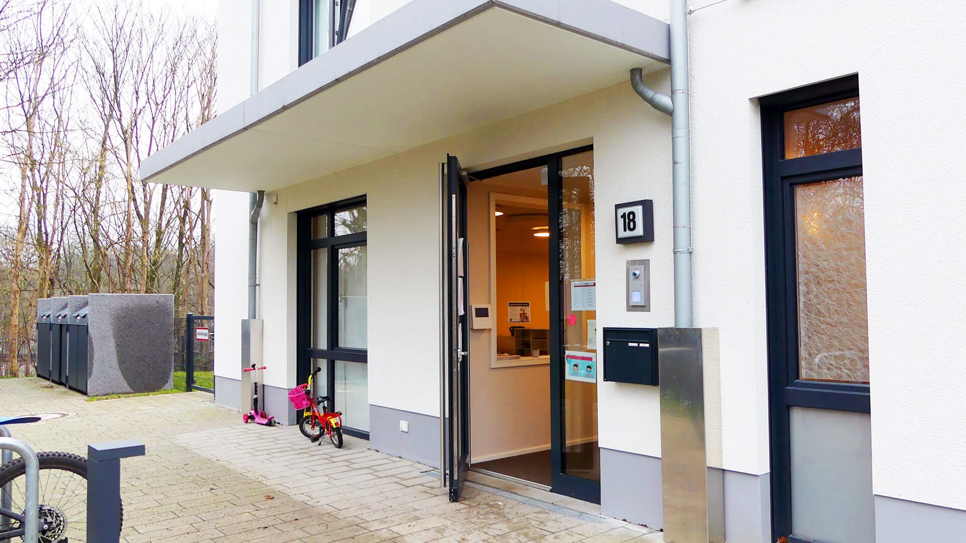 Eingangstür der Kindertagesstätte mit Fahrrädern und Kinderroller