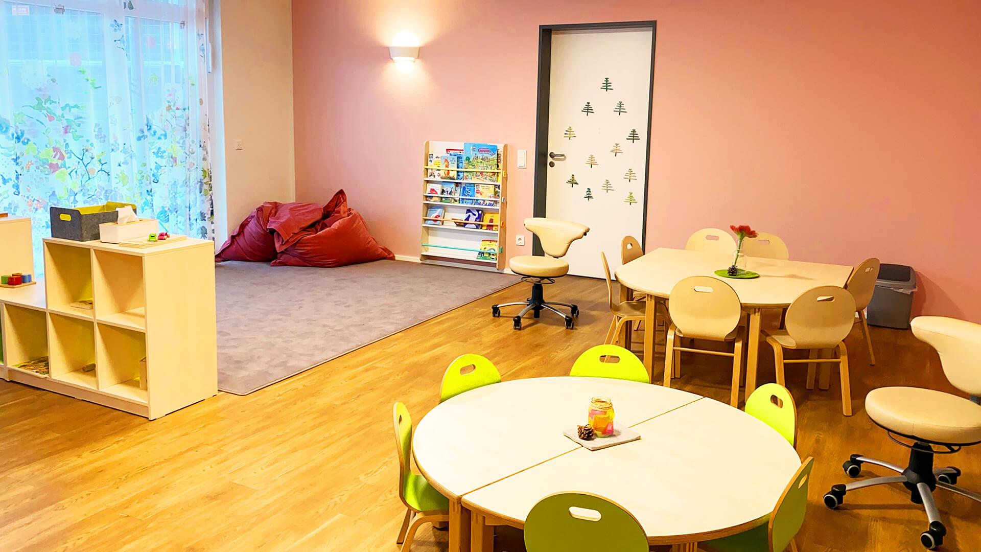 Gruppenraum der Kita in Essen-Rüttenscheid - Mit großen Sitzsäcken auf Teppich, runden Tischen und Stühlen für viele Kinder