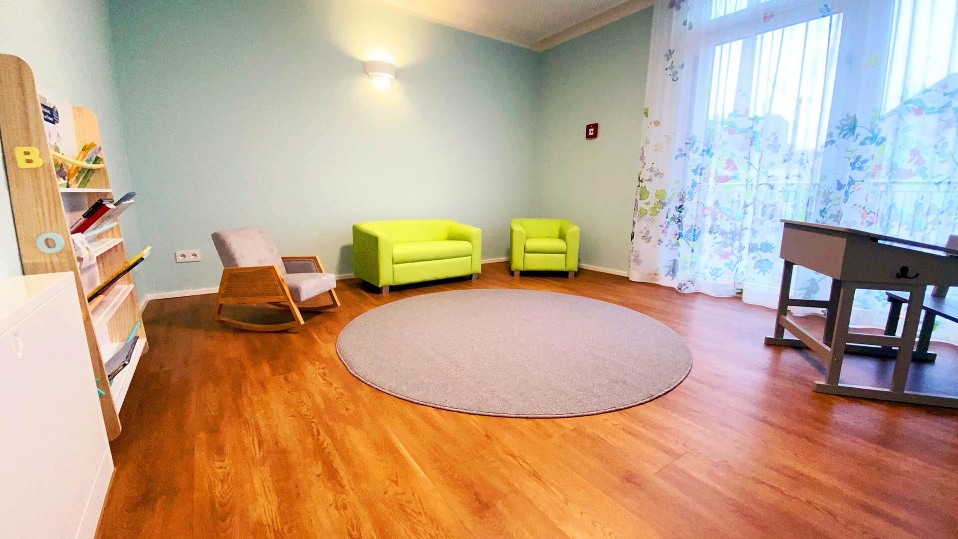 Lese-Ecke mit Bilderbüchern, Sesseln, Schaukelstuhl und großen Fenstern